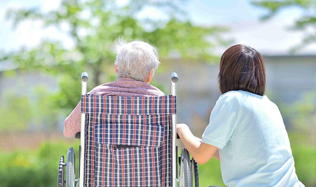 車椅子の老人を介護している写真