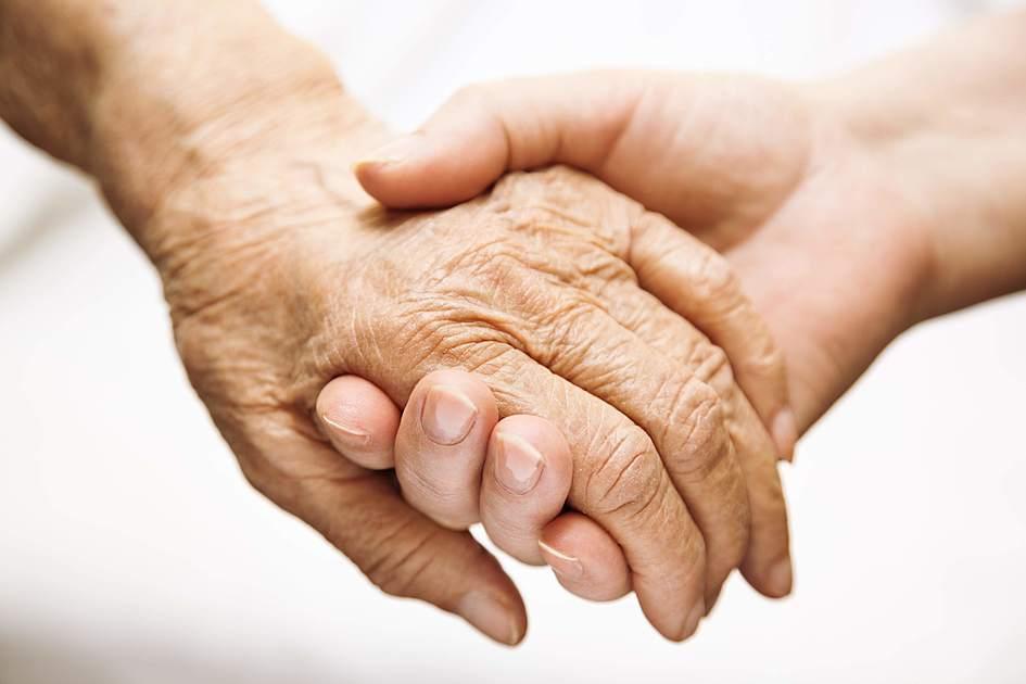 老人の手を握っている写真