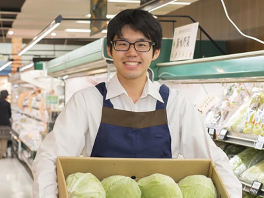 スーパーでキャベツを運んでいるスタッフの写真