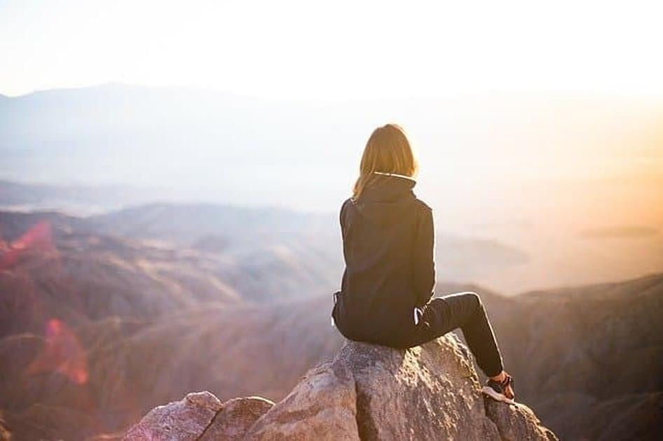 崖の上で風景を眺めている画像