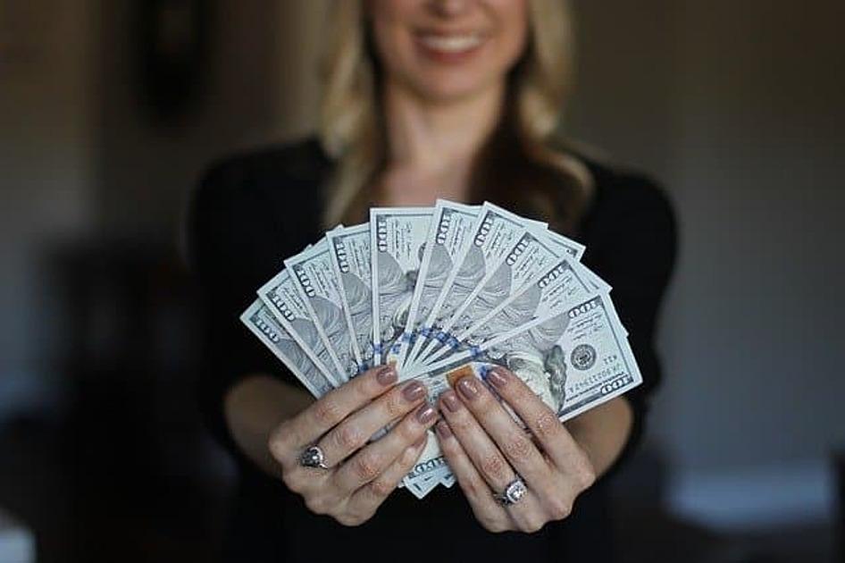 女性がお札を持っている画像