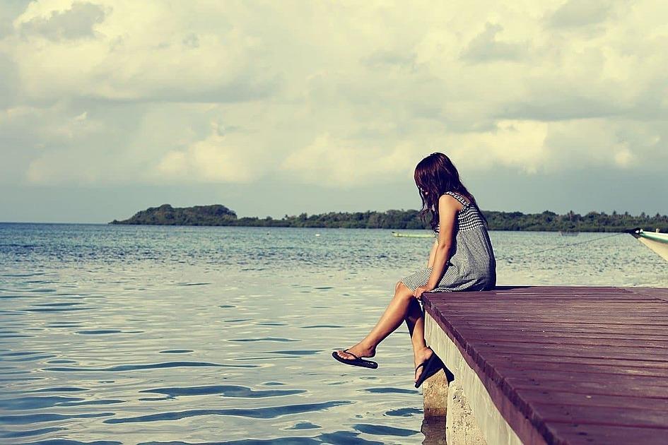 少女が海で暇つぶしをしている画像