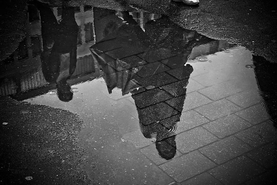 雨の水たまりに影が映る写真