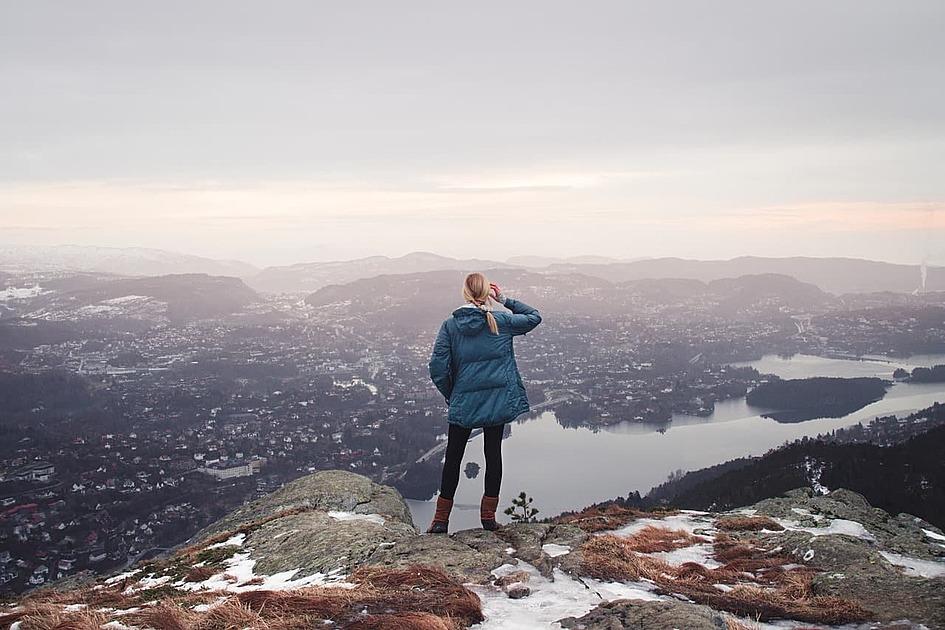 山の上で街を見下ろす女性の写真