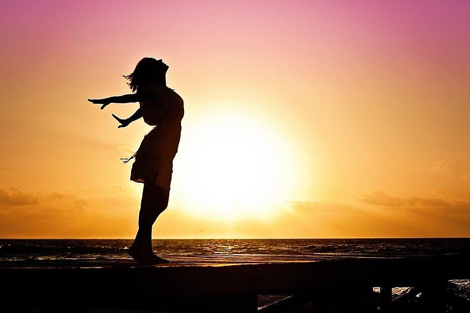夕日に照らされる女性のシルエットの写真