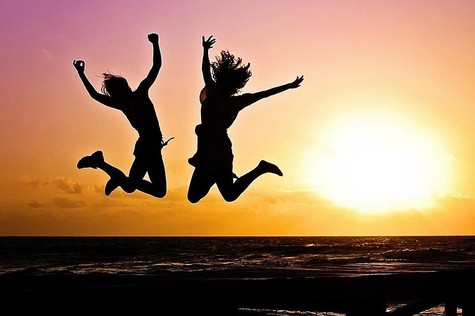 夕日の海で二人が飛び上がっているシルエット写真