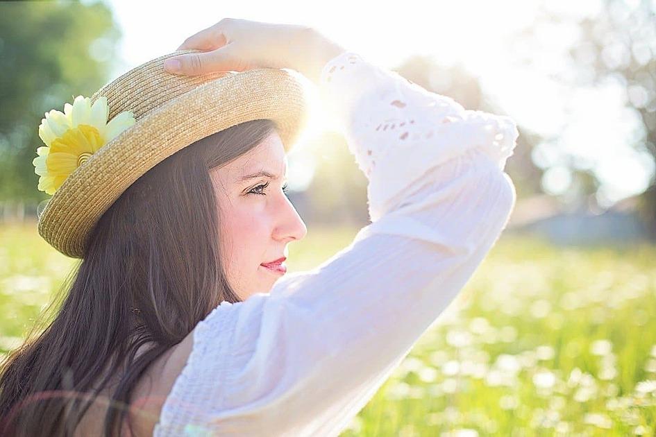野原で麦わら帽を手で押さえた女性の写真