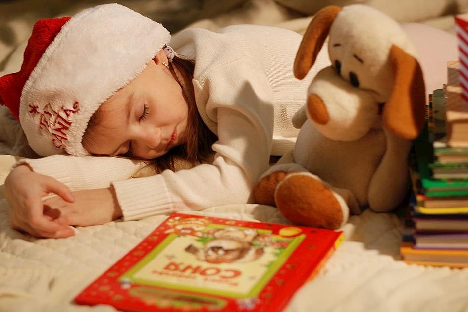 本の隣で女の子が眠っている写真