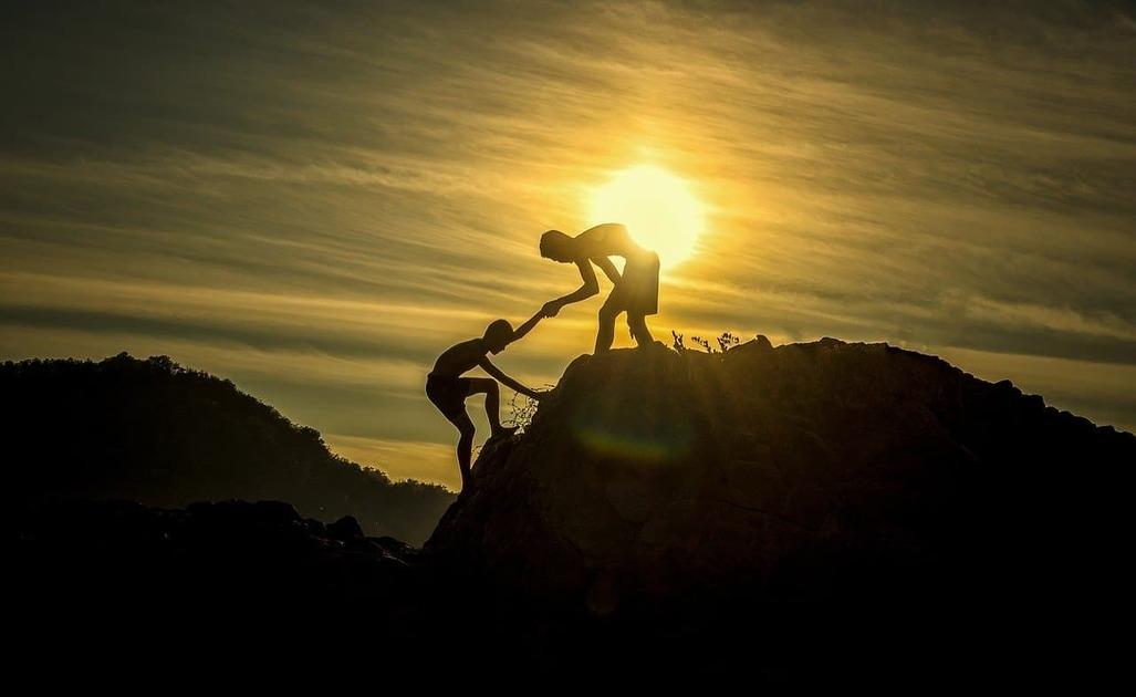 崖の上で人に手を貸している