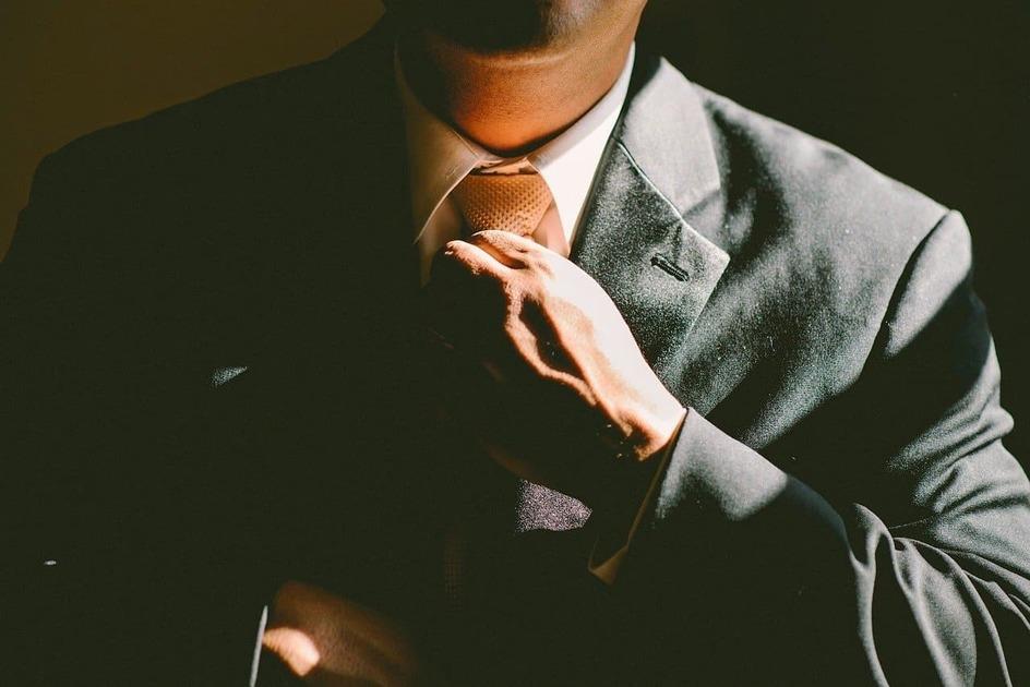 スーツでネクタイを締め直す