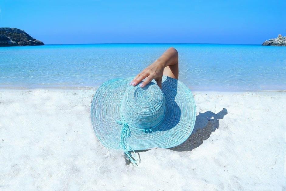 水色のハットをかぶってビーチにいる