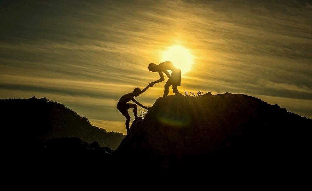 夕日の中で崖を登るのに協力している