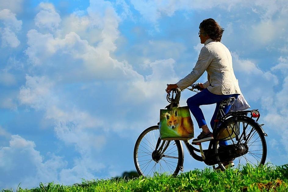 青空で男性が自転車をこんでいる