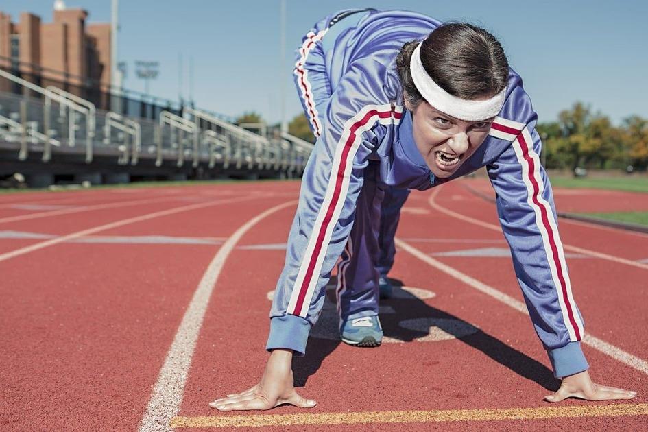 陸上競技場でクラウチングスタートをしている女性