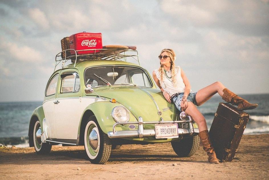 車と大きな旅行バッグの女性