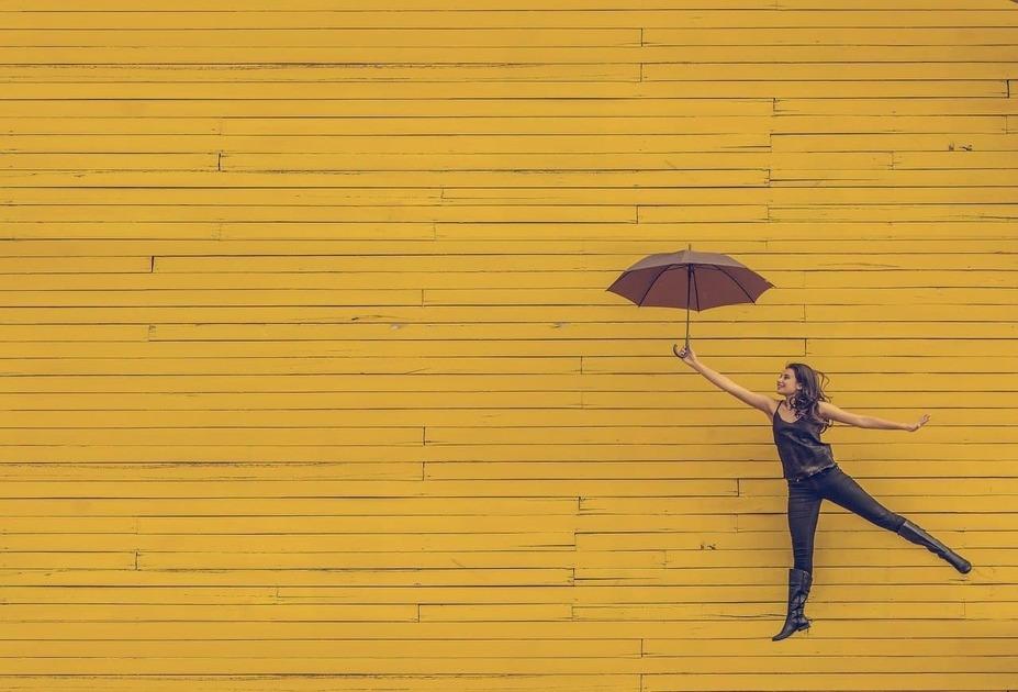 黄色い背景に傘を持って飛んでいる女性