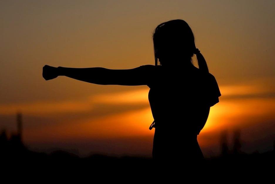 夕日でパンチをする女性